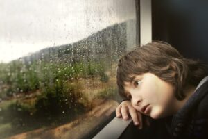 boy looking out window of train